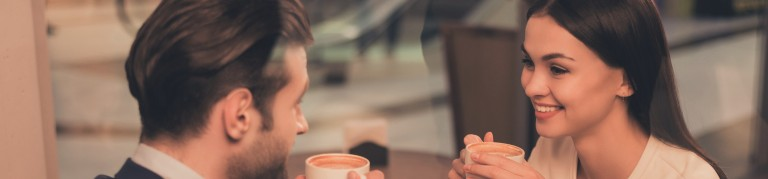Portrait of lovely romantic couple sitting in a cafe with coffee